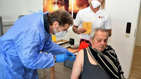Der Mediziner Hubert Schröder impft Anton Boll, während Rettungssanitäterin Bilkay Keller vom Roten Kreuz den Impfpass bereithält. Foto: Michael Lang/DRK Odenwald