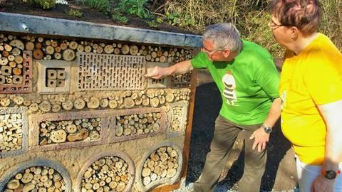 Marion und Joachim Bernd Keller sind besonders stolz auf das aus Lehmstein gebaute Insektenhotel, die Attraktion auf dem neu angelegten Bienenlehrstand. Foto: Günter Weinsheimer  Foto: Günter Weinsheimer