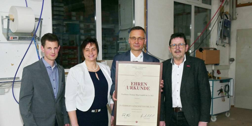 Klaus Zeller (rechts) und Holger Faust (links) überreichen dem Ehepaar Maul eine Urkunde. Foto: Stock