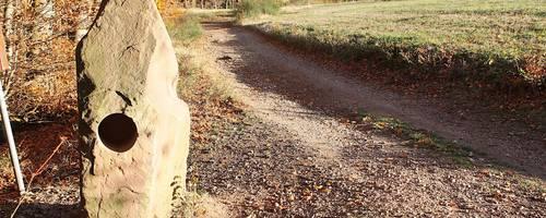 Der Summstein besteht aus lokalem Sandstein. Auf der Harfe (rechts) spielt der Wind seine Lieder. Foto: Katja Gesche