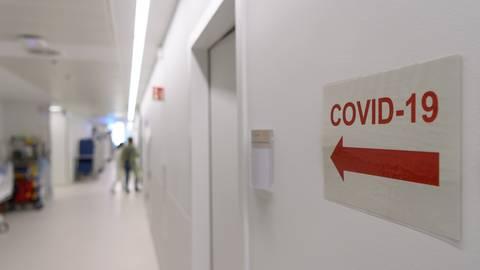 """Ein Richtungspfeil zum """"Covid-19"""" Bereich klebt vor einer Corona-Intensivstation an der Wand.  Symbolfoto: dpa"""