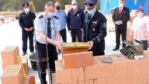 Wehrführer Uwe Diefenbach (vorne links) verschließt die Kapsel mit den Erinnerungen an den Tag der Grundsteinlegung für das neue Feuerwehrhaus mit Containerhalle auf dem Hettenhainer Rabenkopf. Foto: Martin Fromme