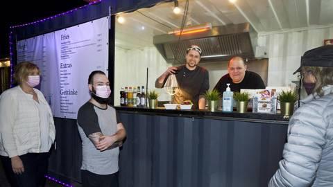 """Philipp Lenertz und Chef Bernd Zehner (re.) in der """"Beefbox"""" servieren hungrigen Kunden einen Cheeseburger. Foto: Mallmann/AMP"""