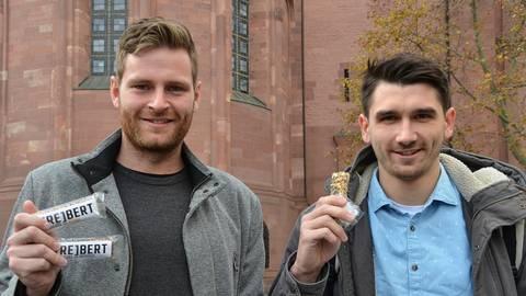 """Die Sportstudenten Eric Galinski (links) und Axel Neumann präsentieren ihre Müsliriegel-Kreation. Entwickelt haben sie den """"[Re]bert"""" aus Treber, den Rückständen des Braumalzes, als Vierer-Team. Foto: Jochen Werner"""