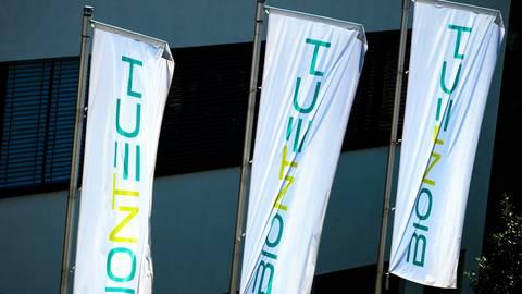 Am Hauptsitz von Biontech in Mainz wehen Fahnen mit der Schriftzug des Unternehmens. Foto: dpa