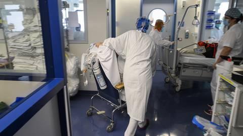 Pflegerinnen eines Krankenhauses verlegen einen Corona-Patienten auf die Abteilung für Intensivpflege. Foto: dpa/Alessandro Della Valle