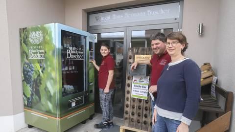 Hans-Jonas, Manfred und Beke Buscher (v.l.) präsentieren ihren Automaten für Wein und Eier vor ihrem Bechtheimer Weingut. Foto: pakalski-press/Andreas Stumpf