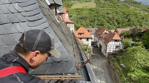 In schwindelerregenden Höhen reinigt Facharbeiter Mario Sam die Regenrinnen am Dach von St. Peter. Foto: Karl-Peter Weis