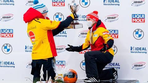 Der Kniefall von Altenberg: Skeleton-Weltmeisterin Tina Hermann (r.) bekommt von Jacqueline Lölling den Siegerpokal. Foto: imago