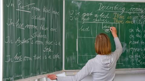 Eine Lehrerin schreibt an die Tafel. Foto: dpa