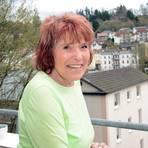 Elfie Reitz hat von ihrem Balkon aus den Kurpark im Blick. Dort wird sie Gläser spülen und Auskünfte geben. Foto: wita/Martin Fromme