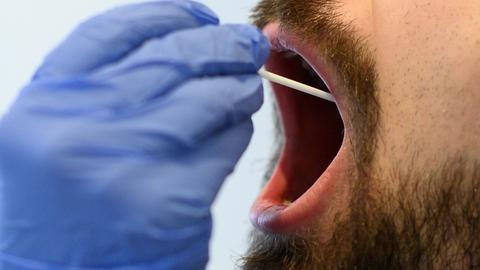 Bei einem Mann wird ein Mundabstrich für einen Corona-Test durchgeführt. Symbolfoto: Bernd von Jutrczenka/dpa