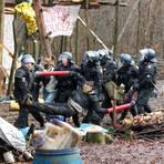 Polizisten tragen drei Aktivisten, die ihre Arme in Metallrohre gesteckt und sich so miteinander verbunden haben, aus dem letzten verbliebenen Camp im Dannenröder Forst.  Foto: Nadine Weigel/dpa