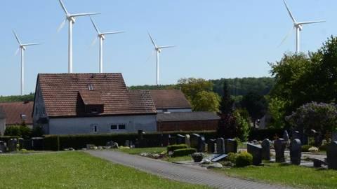Fotomontagen wie diese wurden vor der zweiten Informationsveranstaltung zum Windpark verteilt. Die Anlage auf dem Gebiet der Gemeinde Fernwald (mit Pfeil markiert) wird nicht kommen. Fotomontage: Vogler