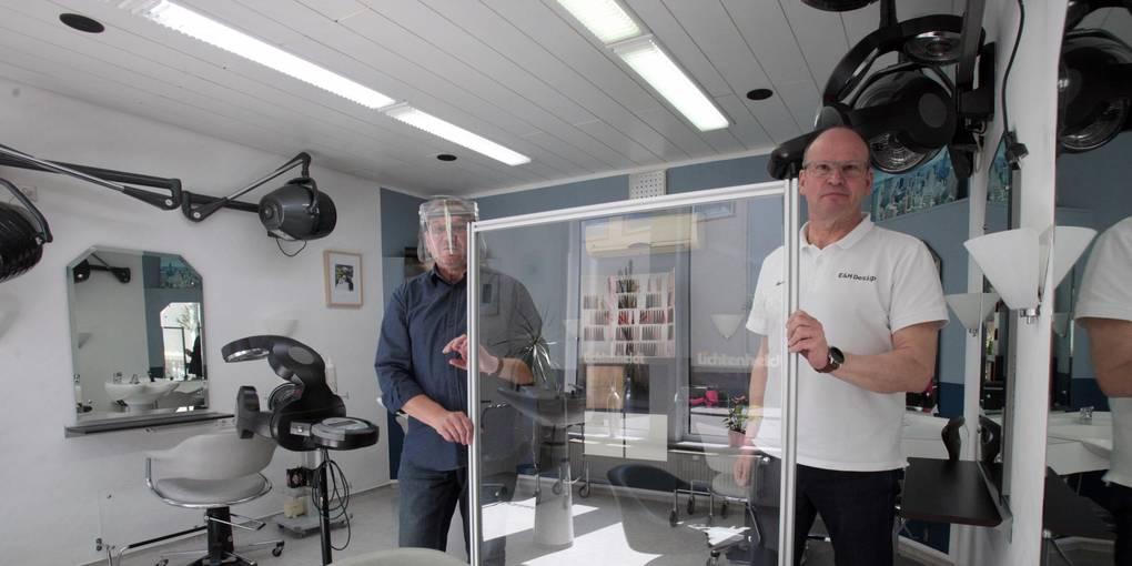 Rüdiger Lichtenheldt (l.) mit Schutzmaske und Sigurd Emt bauen Trennwände zwischen den Kundenplätzen auf. Foto: BK/Axel Schmitz