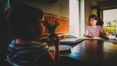 Während der achtjährige Rafael im Homeschooling am Küchentisch noch an seinen Schulaufgaben sitzt, lässt sich seine kleine Schwester Rosalie ein Stück Kuchen schmecken. Foto: Mechanezidis