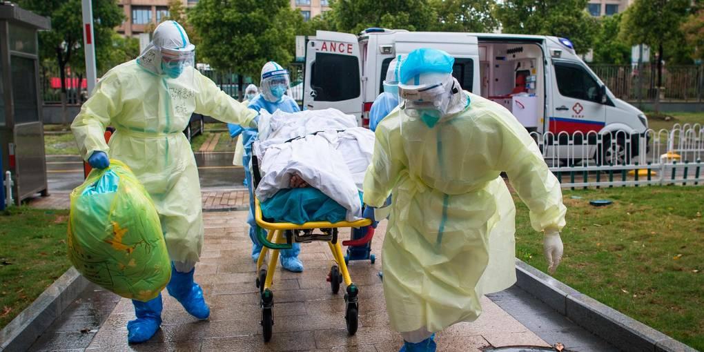 Corona in Wuhan: Medizinisches Personal, das aufgrund der Pandemie Schutzanträge trägt, rollt einen Patienten ins Krankenhaus. Foto: dpa