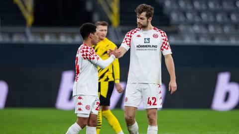 Die Mainzer Phillipp Mwene (l) und Alexander Hack (r) klatschen sich nach dem Spiel bei Borussia Dortmund ab. Foto: dpa