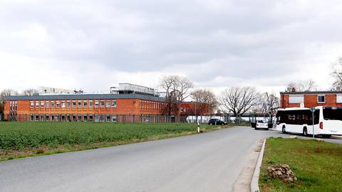 Das Impfzentrum Kastengrund in Hattersheim. Es ist mit Metallzaun und Stacheldraht gesichert. Links im roten Ziegelsteingebäude wird geimpft. Hinter den beiden PKW ist das weiße Empfangszelt zu sehen. Links daneben der Haupteingang. Fotos: Dietmar Elsner