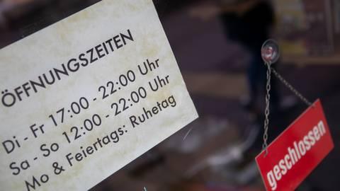 """Ein """"Geschlossen""""-Schild hängt neben den Informationen zu den Öffnungszeiten einer Gaststätte. Foto: dpa"""