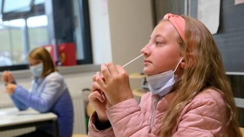 """So geht das: Viertklässlerin Lucia zeigt, wie man mit einem Wattestäbchen Nasensekret für den Corona-Selbsttest """"sammelt"""". Foto: Frank Rademacher"""