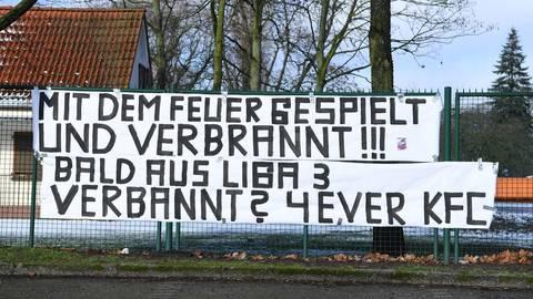 Die treuen Uerdinger Fans haben mit Spruchbändern  an der sanierungsbedürftigen Grotenburg-Kampfbahn in Krefeld ihre eigene Meinung zum schiefgegangenen Investoren-Modell beim KFC. Foto: imago