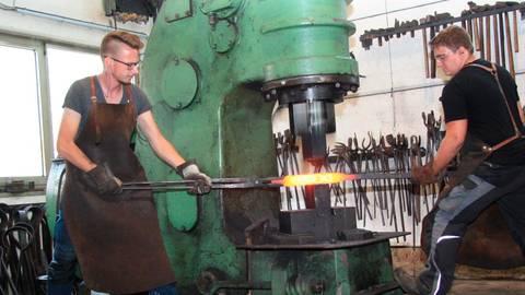 Luca Gebert (links) und Christian Punga bringen den glühenden Stahl mithilfe eines 200-Kilogramm-Lufthammers in die gewünschte Form. Die benötigten Werkzeuge, die hinten an der Wand hängen, stellen die Mitarbeiter selbst her.  Foto: Agathe Markiewicz