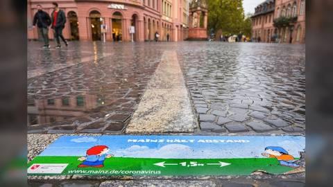 Ein Bodenaufkleber auf dem Mainzer Marktplatz fordert die Bürger zum Abstandhalten auf. Archivfoto: dpa