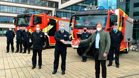 Brandschutzdezernent Peter Neidel (r.) überreicht symbolisch einen Schlüssel.  Foto: Jung