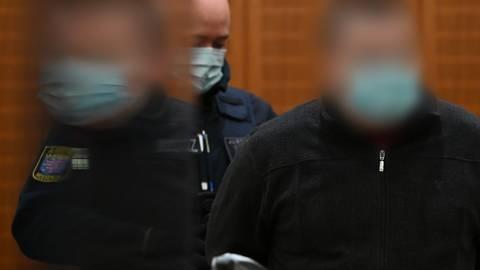 Der Angeklagte (rechts) wird zu Beginn eines Mordprozesses von einem Justizbeamten in den Gerichtssaal des Landgerichts Frankfurt geführt und spiegelt sich dabei in einer Plexiglasscheibe. Foto: dpa