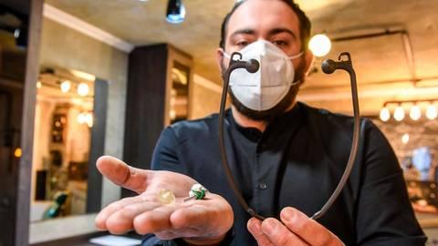 """Friseurmeister als Erfinder: Enzo Olizzo hat den Maskenhalter """"Ohrlizzo"""" entwickelt. Inzwischen gibt es davon bereits die zweite Generation (rechts). Foto: Katrin Weber"""