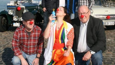 Oldtimer-Freunde von links und rechts des Rheins werben gemeinsam mit Dr. Pille Palle (Gianna Matysik, Mitte) von den Clown-Doktoren für die Benefizaktion. Foto: Christine Tscherner