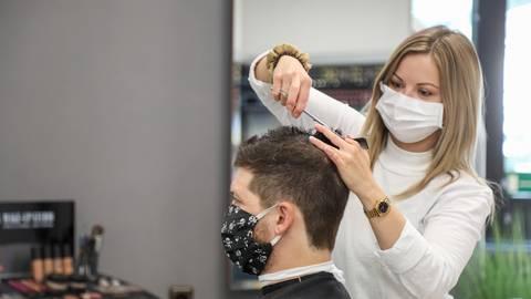 """Frisöre und Kunden müssen jetzt Maske tragen - Anja Bassenauer vom """"City Frisör"""" und ihr Kunde Adrian machen es vor. Foto: Guido Schiek"""