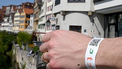 Eine Hand mit einem einem Armband mit einem Tagesticket für Tübingen nach einem Corona-Schnelltest liegt auf einem Brückengeländer vor der Kulisse einer historischen Häuserzeile.  Foto: dpa