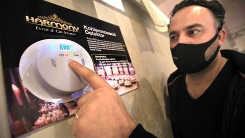 Ali Sanli vor einem  CO-Detektor. Ein gutes Dutzend dieser Geräte sind samt Lüftungsanlage im Veranstaltungsraum installiert. Sie melden, wenn gelüftet werden muss. Foto: hbz/Michael Bahr