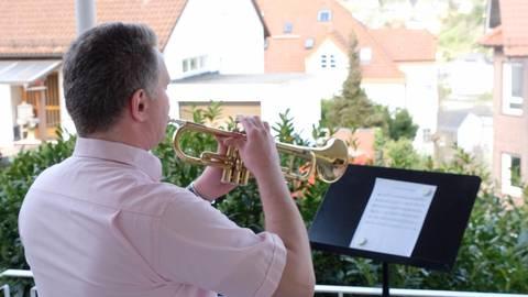 Vom heimischen Balkon für ganz Bad Schwalbach: Kantor Patrick Leidinger spielt ein Osterlied auf der Trompete. Foto: Martin Fromme