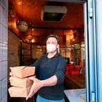 Inhaber Ben Gustke übergibt die Speisen (unter anderem Kochkässchnitzel mit Bratkartoffeln und Salat) Corona-konform an der Hintertür.Foto: Dirk Zengel