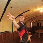 Im romantischen Keller des Siefersheimer Dorfgemeinschaftshauses trainiert Niko Springer unter einer Funzel für seine Auftritte im Rampenlicht der großen Dart-Turniere. Foto: BK/Axel Schmitz