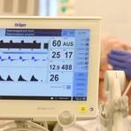 Auf der Covid-Station einer Klinik versorgt ein Intensivpfleger einen Patienten, der an ein Beatmungsgerät angeschlossen ist. Foto: dpa