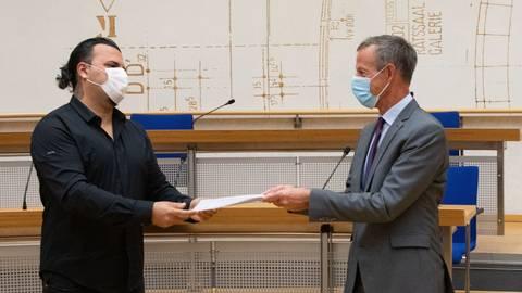 Oktay Kücük (links) übergibt Oberbürgermeister Udo Bausch die Liste der Unterschriften, mit der die Anwohner der Georg-Treber-Straße gegen die Strafzettel wegen Falschparkens protestieren.                Foto: Volker Dziemballa
