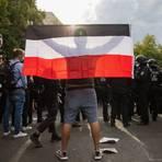 Ein Mann hält eine Reichsflagge bei einem Protest gegen die Corona-Maßnahmen. Foto: dpa