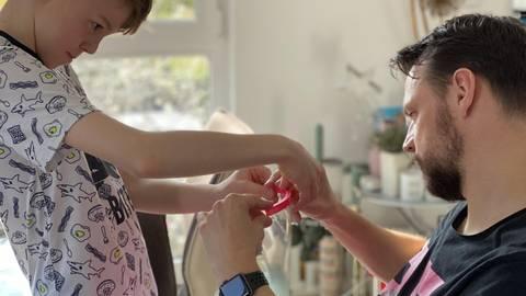 Jake hilft beim Zusammensetzen der Masken; Matthias Mangold zeigt seinem Sohn, wie es geht. Foto: Mangold