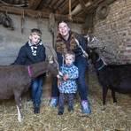 Sabrina Dörnen mit ihren Söhnen Finn (links) und Nils mit den Thüringer Waldziegen im Stall. Foto: Vollformat/Robert Heiler