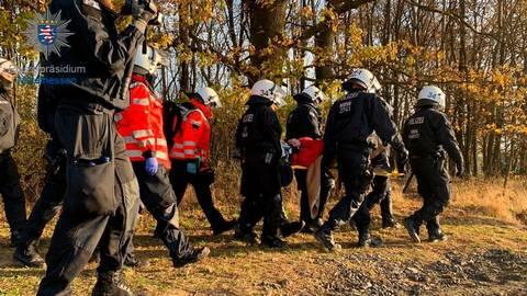 Polizisten transportieren die Aktivistin, die im Dannenröder Forst von einem Tripod gefallen ist, aus dem Wald. Bildquelle: Polizeipräsidium Mittelhessen (Twitter)