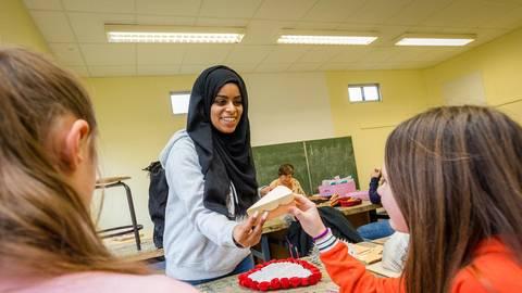 """Auch wenn Basteln nicht ihre Stärke ist: Mit den Schülern im """"Paper Art""""-Projekt kommt Nada Seleman gut klar. Foto: BilderKartell/Selak"""