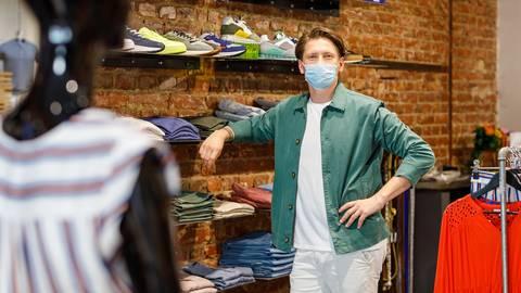 """Stefano Muzio arbeitet in der Boutique """"Laufsteg"""" am Michelsberg in Wiesbaden und hat noch keine Proteste von Kunden gegen den Mundschutz erlebt. Allerdings müssen gerade jüngere Kunden häufig an die Maske erinnert werden. Foto: Jörg Halisch"""