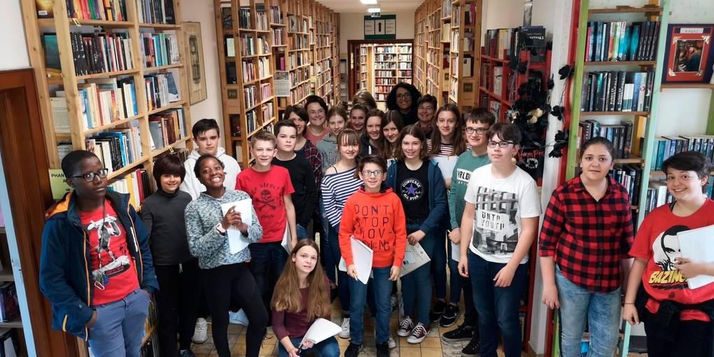 Auf Erkundungsgang durch die Phantastische Bibliothek Wetzlar: Die Klasse 7b mit der Lyrikerin Safiye Can (hinten Mitte) und ihrer Klassenlehrerin Ivonne Schweitzer (hinten rechts) im ersten Untergeschoss, wo ein Großteil der Science Fiction-Texte untergebracht ist.  Foto: Maren Bonacker