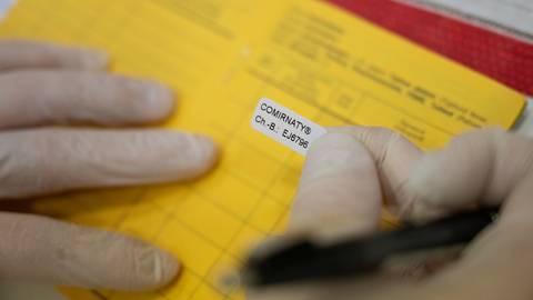Der Impfnachweis für den Corona-Impfstoff Comirnaty von Biontech/Pfizer wird in einen Impfausweis eingeklebt. Foto: Marijan Murat/dpa