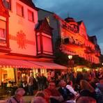 """Bei """"Assmannshausen in Rot"""" senden Strahler rotes Licht an die Hausfassaden auf der Rheinuferstraße. Das dreitägige Fest zieht viele Besucher an. Foto: Heinz Margielsky"""