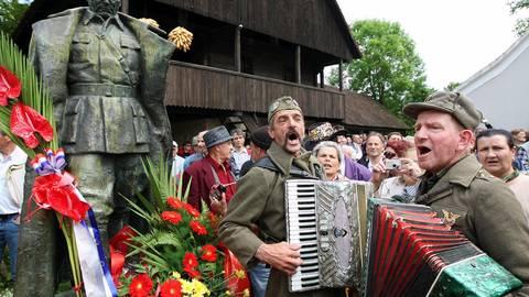 Nachruhm: Zwei als Partisanen des früheren jugoslawischen Präsidenten Tito verkleidete Bosnier singen und spielen im Mai 2010 Akkordeon neben einer Tito-Skulptur vor Titos Haus und Gedenkstätte im kroatischen Kumrovec. Archivfoto: dpa